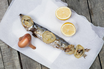 Horizontal image of one baked mackerel fish on white paper