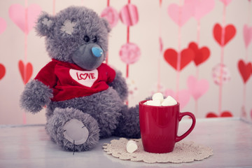 Teddy bear with hot drink in a red mug and marshmallow