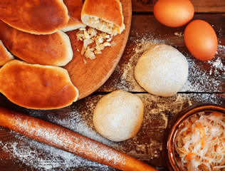 Traditional pies with cabbage. Dough, rolling pin and pastry on