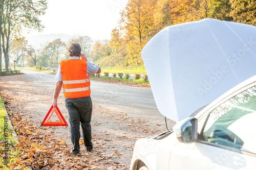 Autospanne, Fahrer stellt Warndreieck auf und öffnet Motorhaube - 77681491