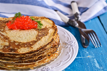 A stack of pancakes with red caviar