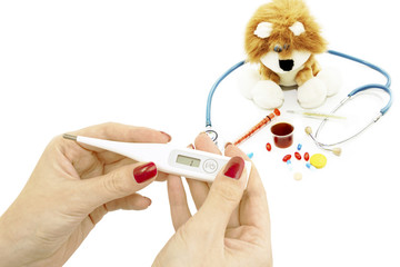 Thermometer in hand and soft toy with a stethoscope