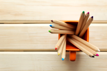 Cup with colorful Pencils on wooden table
