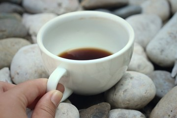 Coffee in a white cup on a background of white stone.