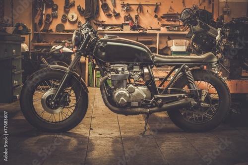 Vintage style cafe-racer motorcycle in customs garage - 77683607