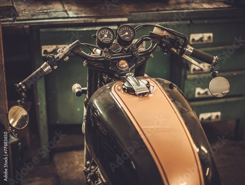 Vintage style cafe-racer motorcycle in customs garage - 77683650