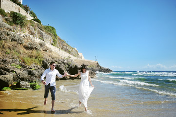 happy couple running on the beach near sea in wedding day