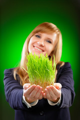 Young business woman holding fresh green grass.