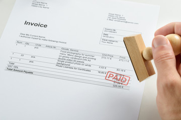 Person Hand Holding Rubber Stamp Over Paid Invoice
