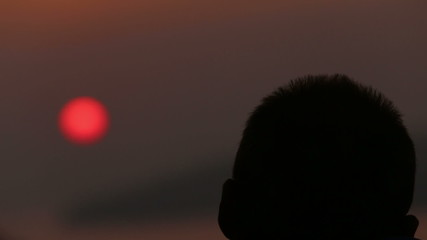 man in glasses admires the sunset over the sea from the hill top