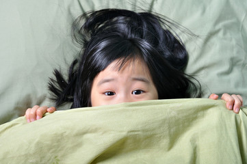 Scared little asian girl hiding behind blanket