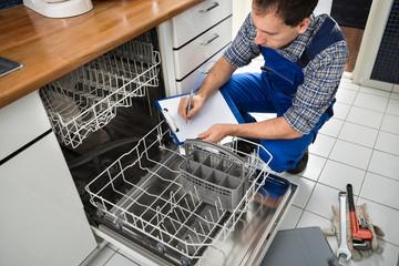 Technician Writing On Clipboard In Kitchen