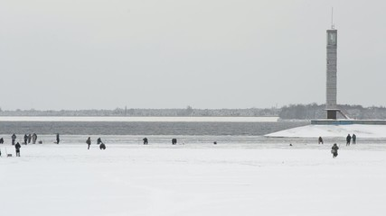 Many winter fishermen angling on ice of water storage reservoir