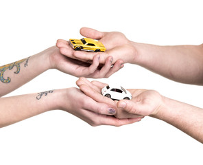 Hands of young couple with miniature cars