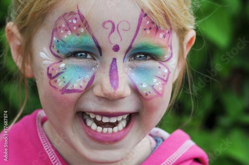 lachendes Mädchen als Schmetterling geschminkt - 77687874