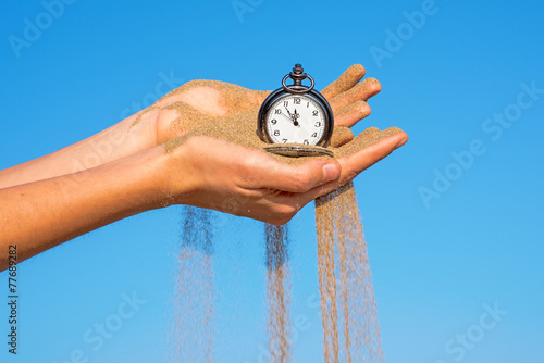 pocket clock in hands and sand flowing - 77689282