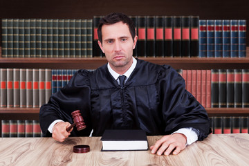 Confident Judge Striking Gavel In Courtroom