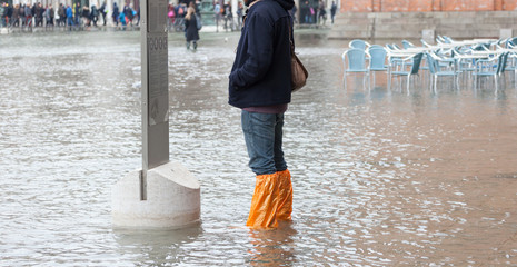 Close Up of legs with boots due to the high water in Venice.