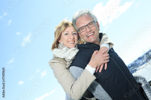 Portrait of happy senior couple in winter season - 77691624