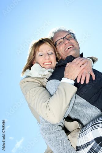 Portrait of happy senior couple in winter season - 77691636
