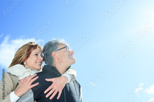 Portrait of happy senior couple in winter season - 77691659