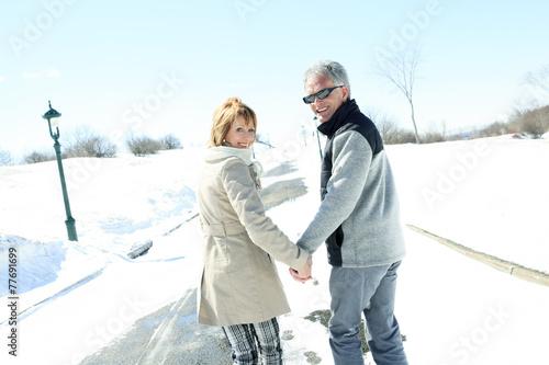Portrait of happy senior couple in winter season - 77691699