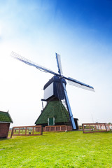 Rotating wooden windmill on farm field in Holland