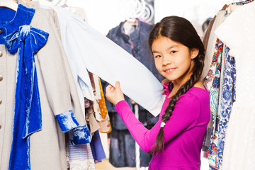 Asian girl with braid between clothes on  hangers