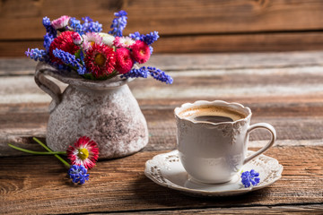 Coffee and spring flowers on old wooden table