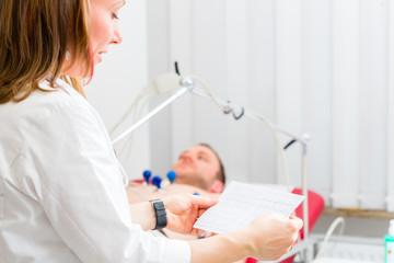 Doktor kontrolliert Patient EKG in Arztpraxis
