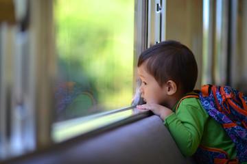 車窓から景色を眺める子供