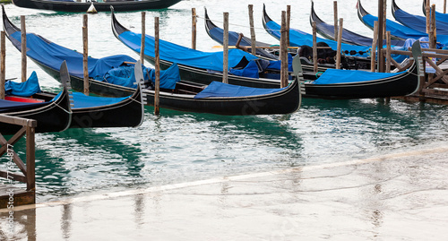 Papiers peints Gondoles Venetian gondolas with high tide.