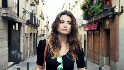 Sad, pensive beautiful woman walking in the city