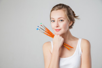 Close-up of smiling artist-girl with paintbrushes.