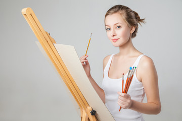 Artist with paintbrushes and canvas over white