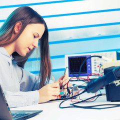 Girl repairing electronic device on the circuit board