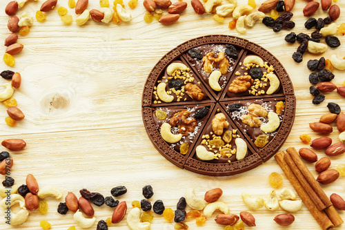 Dessert chocolate pizza with raisins and nuts - 77697631