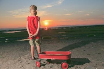 Cute boy playing with beach toys on beach sunset.
