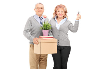 Mature couple holding moving boxes and keys