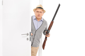 Senior with rifle bursting through a door