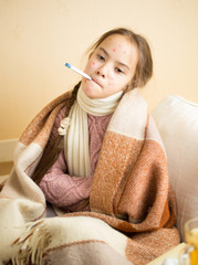 little girl with chickenpox holding thermometer in mouth