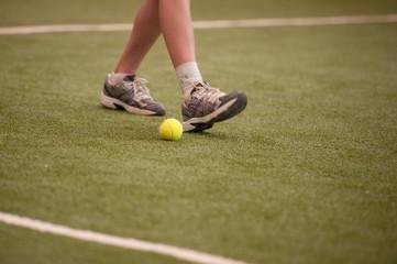 Tennis player legs and tennis ball