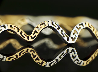 Piece of gold jewellery on black background