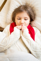 portrait of little girl in sweater ling in bed under blanket