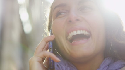 Attractive young woman laughing whilst talking on her phone