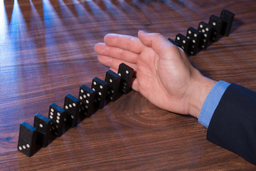 Hand Stopping Dominoes Falling