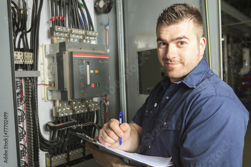 Portrait of an happy worker in a factory - 77702499