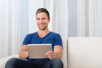 Portrait Of A Smiling Man Holding Digital Tablet