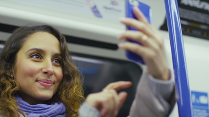 Attractive woman takes a photo on a train in slow motion