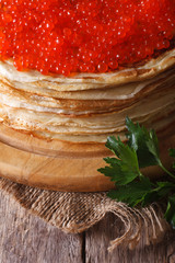 A pile of thin crepes with red caviar close-up. Vertical